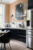 Black kitchen counter, stainless steel fridge-freezer and dining area