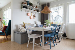 Wooden dining table with white and blue chairs and dog sitting on bench