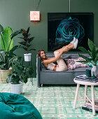Junge Frau auf grünem Polstersofa liegend im Wohnzimmer mit Zimmerpflanzen und grüner Wand
