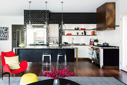 Black and white wall tiles in an open kitchen with an island, in the foreground a red armchair