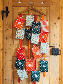 DIY Advent calendar made of colourful paper bag hanging on a wooden door