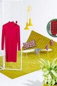 Rotes Kleid am Paravent auf gelbem Teppich mit Gittermuster