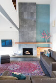 Grey leather sofa set and fireplace with floor-to ceiling concrete chimney breast in lounge