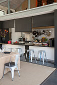 Counter and barstools in open-plan kitchen below gallery