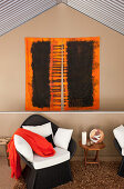 Artwork on wall above rattan armchair with seat cushions and scatter cushions and small side table