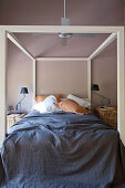 Four-poster bed with dark blue bedspread in bedroom with brown wall
