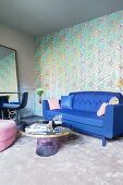 Blue sofa against gold-patterned wallpaper in elegant living room