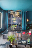 Table with metal canopy in dining room with blue ceiling