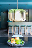 Fruit bowl below ceiling lamp and bar stools in background