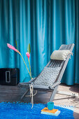 Grey wooden chair and pink flowers in front of blue curtain
