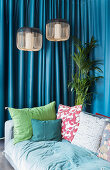 Various scatter cushions on sofa in front of petrol-blue curtain