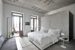 Doppelbett mit weißer Bettwäsche vor Betonwand im Hotelzimmer