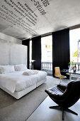 Doppelbett mit weißer Bettwäsche vor Betonwand im Hotelzimmer, im Vordergrund Ledersessel