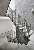 Betontreppen mit Metallgeländer im Treppenhaus