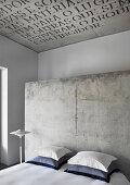 Doppelbett mit Kissen vor Betonwand im Hotelzimmer, Betondecke mit Schrift
