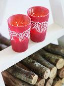 Zwei rote Teelichtgläser mit weihnachtlichem Blättermotiv