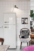 White retro fridge and chair with zebra cushion against white-tiled wall
