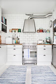 Blue-and-white rag rugs in white country-house kitchen
