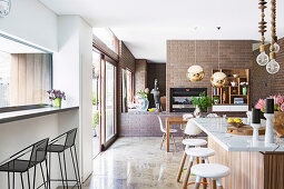 Middle block with marble top in open kitchen with brick wall, dining area in the background