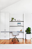 White cupboard and shelf with integrated desk, shell chair in front