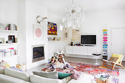 White living room with colorful accessories, reading girls on the carpet