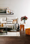 Upholstered sofa with cushions, wall shelf with pictures, side tables and coffee table