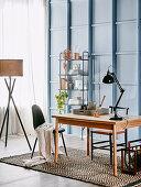 Holztisch mit Gelenklampe, offenes Regal und Stehlampe im Arbeitszimmer