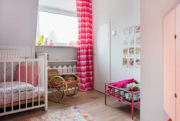 Cot, rocking chair, pink curtains and dolls' bed in girl's bedroom
