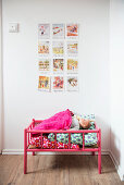 Scandinavian postcards on wall above pink dolls' bed