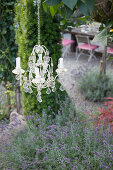 Candle chandelier above bed of lavender in garden
