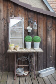 Potted plants, stones and window on old sewing machine base on terrace