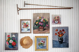 Floral pictures, vintage rakes and hat on white-painted wooden wall