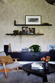 Retro armchair and black furniture in front of floral wallpaper in living room