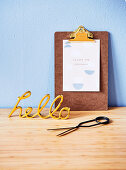 Golden decorative writing and clipboard with a saying on a light blue wall