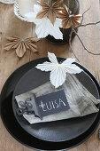 Namensschild auf schwarzem Teller und Blätter aus gefaltetem Papier