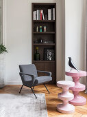 Pink, modern side tables and armchair in front of shelves