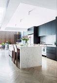 Stone kitchen island in open kitchen with herringbone parquet