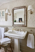 Antique mirror above pedestal sink and vintage stool