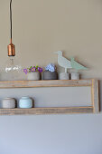 Bird ornaments and miniature ceramic vases on simple wooden shelves