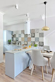 Dining table abutting L-shaped kitchen counter used as partition