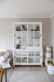 White glass-fronted cabinet and white bamboo baskets in corner