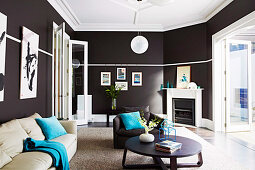 Elegant living room with black walls and white ceiling, upholstered furniture and coffee table