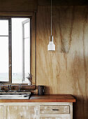 Kitchen base cabinet with sink and pendant lamp in vintage hut