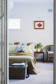 Blick ins Schlafzimmer mit Doppelbett, Nachttisch und Rattanstuhl