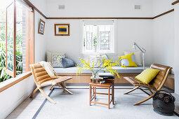 Vintage Lederstühle und Beistelltisch vor eingebauter Sitzbank im Wohnzimmer