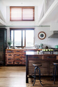 Kücheninsel mit Schubladen aus recyceltem Holz und Vintage Barhocker in offener Küche, im Hintergrund Schubladenschrank