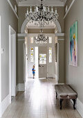 Upholstered bench and chandelier in the hallway with wooden floorboards and arches, toddler in the background