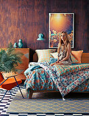 Young woman on double bed with colorful bedding in front of wooden wall