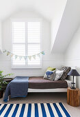 Children's bed with pillows, tree trunk as bedside table with lamp in white attic room