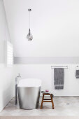 Freestanding bathtub in white attic bathroom